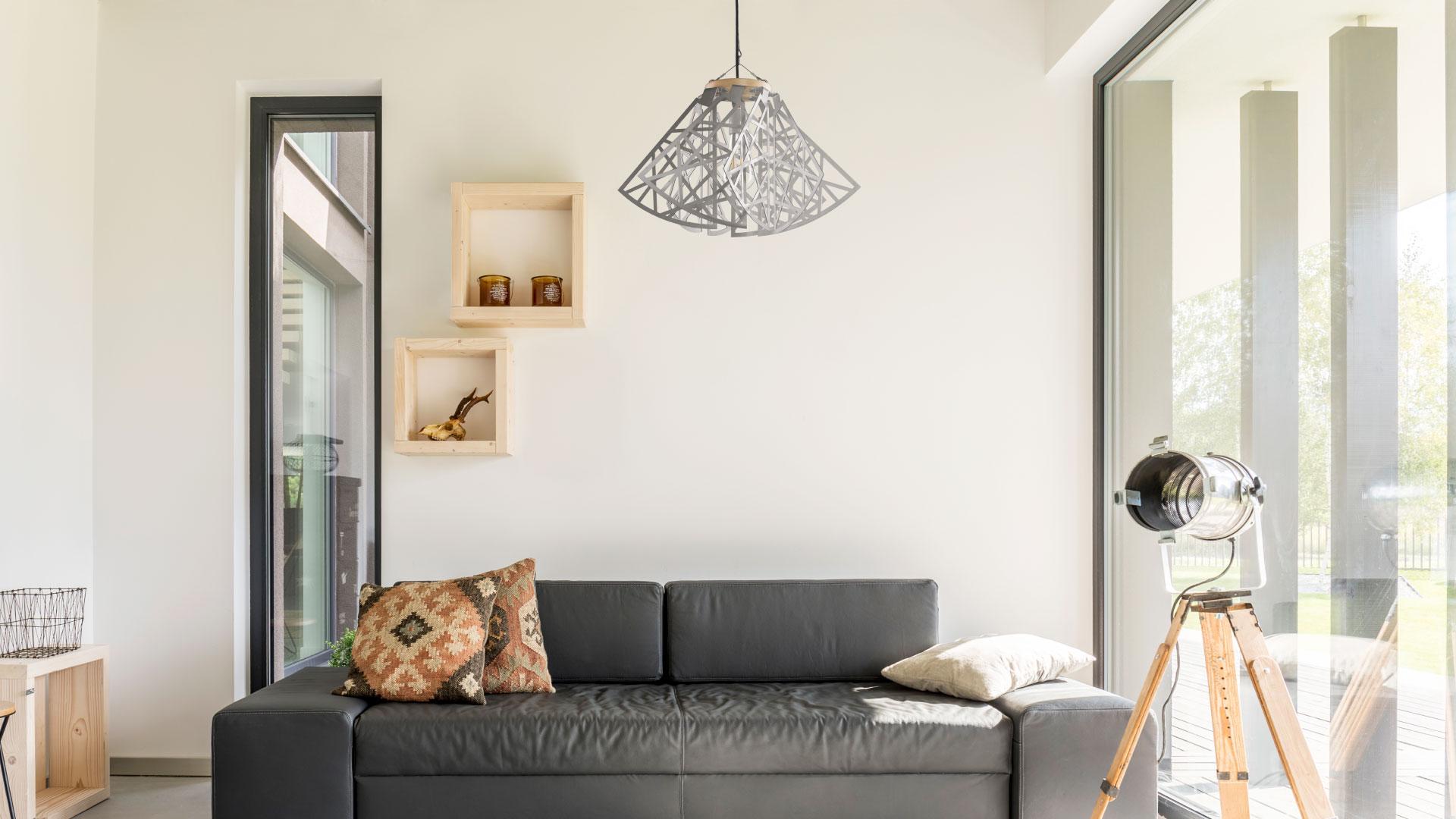 Lámpara CROÓ Rogal recta en salón con sillón negro y ventana lateral